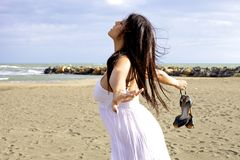 Woman dancing on the beach with eyes closed and wind blowing Stock Images