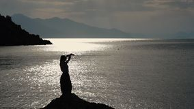 The pretty woman dancing on a rock by the sea in slow motion at sunset
