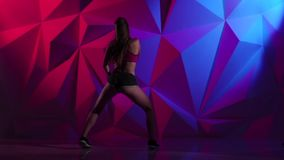Woman dancing booty in shorts on bright graphic background. Slow motion stock footage