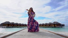 Woman dancing on bridge on beach with transparent water of ocean in Maldives. Woman dancing on bridge on beach with pure transparent water of ocean in Maldives stock footage