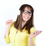 Woman dancing with earbuds / headphones listening to music on mp Stock Photography