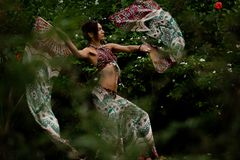 Woman dancing with a fans on natural tropical background royalty free stock photography