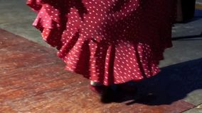 Woman dancing flamenco. Video of woman dancing flamenco in long traditional red skirt with polka dots with focus on her legs stock footage