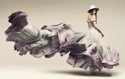 Woman dancing in fluttering purple dress and hat. In studio stock images