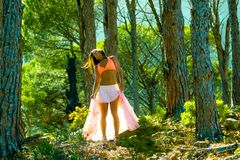 Woman dancing in a forest flicking her hair with trees in the background. Royalty Free Stock Photography