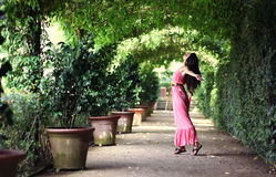 Woman dancing in garden passage. Young woman in pink long dress dancing along beneath the garden green rooftop royalty free stock photos