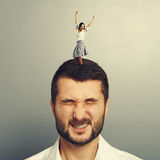 Woman dancing on the head of dissatisfied man Royalty Free Stock Images