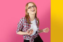Woman dancing with headphones listening to music on smartphone. Royalty Free Stock Image