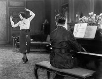 Woman dancing while her husband is playing the piano Stock Photos