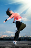 Woman dancing hip hop over blue sky and sun. Beautiful woman dancing hip-hop modern style over urban city landscape, blue sky and sun Royalty Free Stock Photo