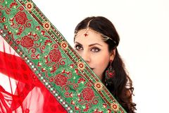 Woman dancing Indian dance in national dress. A handsome beautiful girl portrait in red Hindu Saree, horn for the Indian dance movement. Indian dancer in Royalty Free Stock Photo