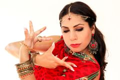 Woman dancing Indian dance in national dress. A handsome beautiful girl portrait in red Hindu Saree, horn for the Indian dance movement. Indian dancer in Stock Photos