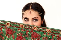 Woman dancing Indian dance in national dress. A handsome beautiful girl portrait in red Hindu Saree, horn for the Indian dance movement. Indian dancer in Royalty Free Stock Photos