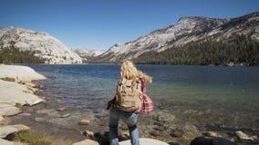 Woman dancing at a lake in Yosemite Park. wanderlust concept stock video