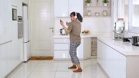Woman dancing while listening music in kitchen stock video