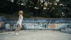 Woman dancing modern choreography in city park, outside. City ruins and graffiti. Young Asian woman dancing modern choreography in city park, outside. City stock footage