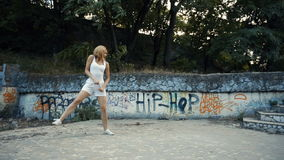 Woman dancing modern choreography in city park, outside. City ruins and graffiti. stock video