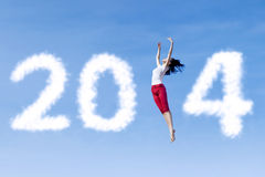 Woman dancing with new year 2014. Excited asian woman is dancing with new year 2014 on the sky Stock Photos