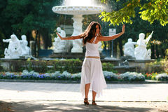 Woman dancing in park. Young woman dancing and turning in park with statues in background stock image