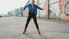 Blonde woman dancing performs modern hip-hop dance posing, freestyle in street, urban. 4K stock footage