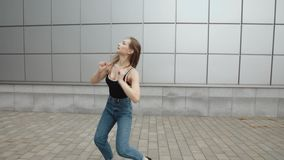 Woman dancing performs modern hip-hop dance posing, freestyle in street, urban