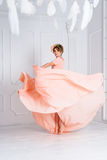 Woman dancing in pink evening dress flying on wind. Waving fabric, fashion shot. Stock Photos