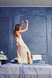 Woman dancing with raised hands on the bed Stock Images