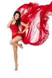 Woman dancing in red flying dress. Over white. Woman dancing in red flying waving chiffon dress as wings on a wind flow. Over white background royalty free stock photo