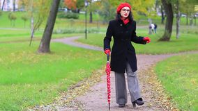 Woman dancing with red umbrella in the autumn park. Elegant woman with glasses and a red umbrella dancing in the autumn park stock video