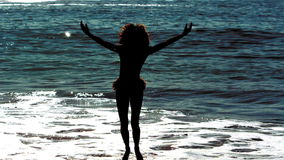 Woman dancing while she is into the sea stock footage