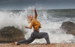 Woman dancing in the sea surf. Performer girl dancing on a splash background in the sea surf stock images