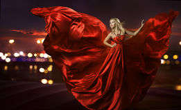 Woman dancing in silk dress, artistic red blowing. Gown waving and flittering fabric, night city street lights Royalty Free Stock Photo