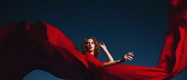 Woman dancing in silk dress, artistic red blowing gown waving and flittering fabric stock photography