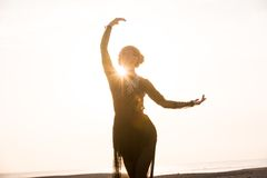 Woman dancing at sunrise Stock Photos