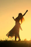 Woman Dancing at Sunset. A woman wearing a long skirt, with long blonde hair, is dancing and spinning, while silhouetted against the evening sky royalty free stock photos