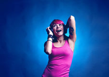 Woman dancing to music. Trendy young woman in pin top with headphones dancing to music, blue studio background stock image