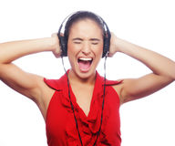 Woman dancing to music with headphones against white background Royalty Free Stock Image