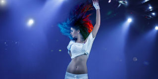 Woman dancing under spotlights. Woman dancing under nightclub or stage spotlights royalty free stock photos