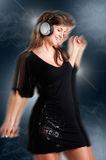 Woman Dancing. Using headphones in a dark background, with motion blur Royalty Free Stock Image