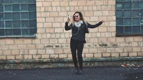 Woman dancing by the wall of the industrial building of brick on the street. Young beautiful woman with headphones and smartphone in hand in mirrored sunglasses stock video