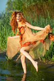 Woman dancing in the water. Red-haired woman in an orange dress dancing in the water Stock Photo
