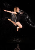 Woman dancing water jumping black background stock image