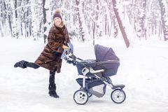 Woman dancing while winter walk with a stroller. Royalty Free Stock Photography