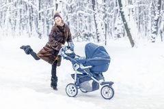 Woman dancing while winter walk with a stroller. Royalty Free Stock Photos