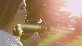 Woman with dandelion clock. Pretty young woman blowing a dandelion clock in the garden stock video footage