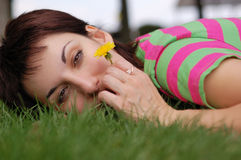 Woman with dandelion lying on green grass Stock Image