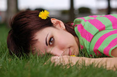 Woman with dandelion lying on green grass Royalty Free Stock Photography