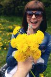 Woman with dandelions in a green spring park outdoors. Young female with yellow dandelions. royalty free stock photo