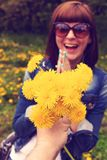 Woman with dandelions in a green spring park outdoors. Young female with yellow dandelions. stock images