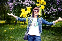 Woman with dandelions in a green spring park outdoors. Young female with yellow dandelions. royalty free stock photos